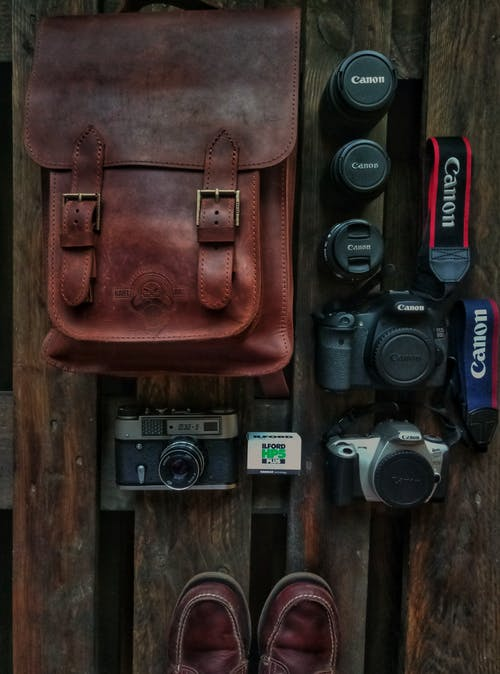 Three Assorted Dslr Cameras Beside Brown Leather Bag
