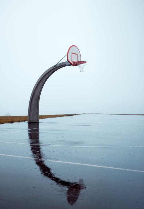 Photo of Empty Concrete Basketball Court on Gloomy Day