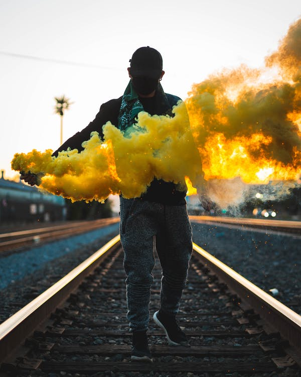 Photo of Man Standing on Train Tracks Holding a Yellow Smoke Bomb