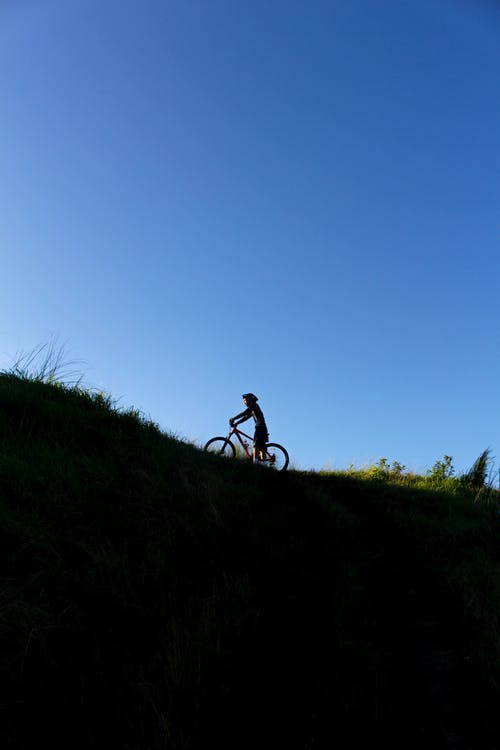 Man Riding Bicycle on Green Grass Field
