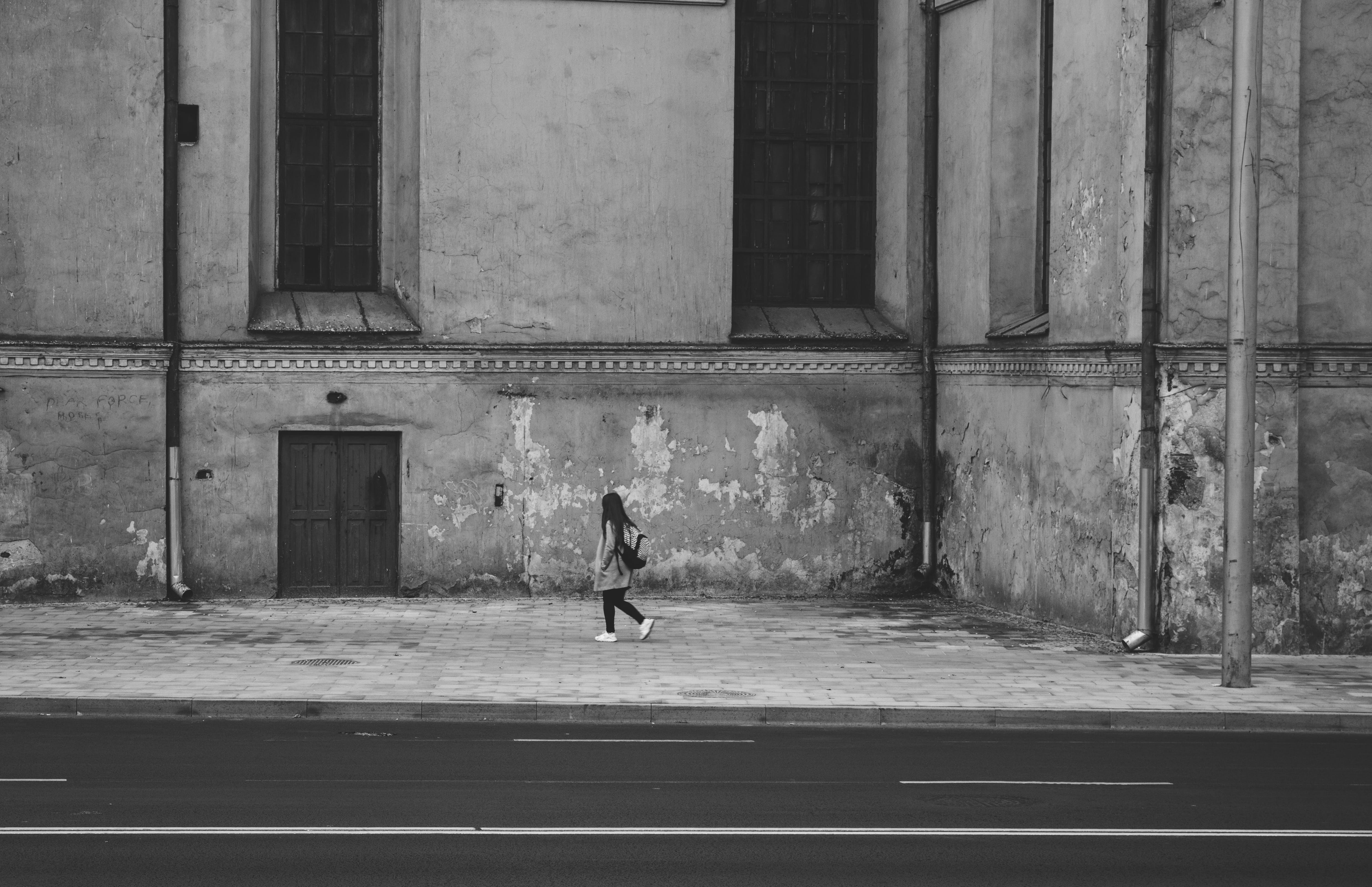 Gray Scale Photography of Woman Walking Near High Rise Building