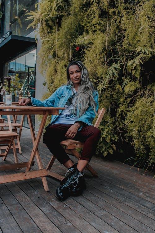 Woman Wearing Maroon Pants Sitting on Brown Wooden Chair