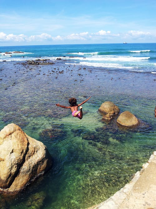 바다 절벽에서 다이빙하는 아이