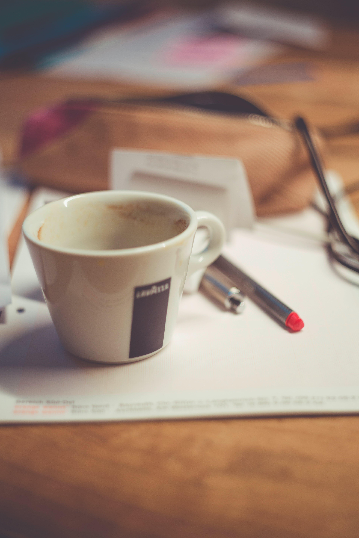White Ceramic Mug on White Table Near Grey Pen