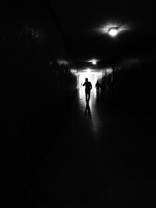 Person Inside Dark Hallway
