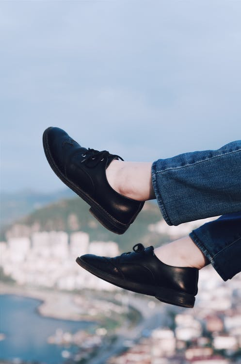 Person Wearing Black Lace Up Low Top Sneakers