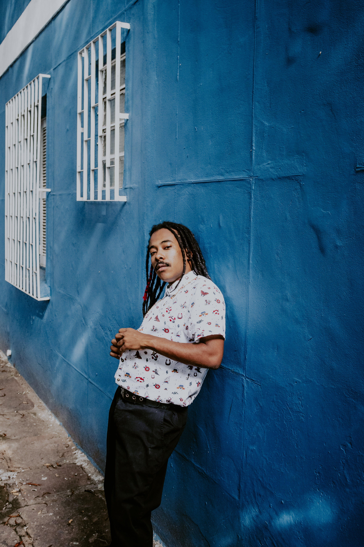 Man Leaning on Blue Wall Near Window