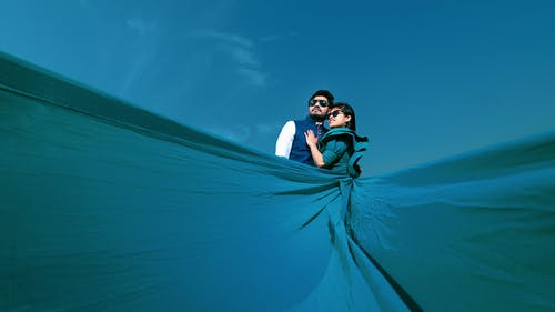 Woman Wearing Blue Maxi Dress Hugging Man Under Clear Blue Sky
