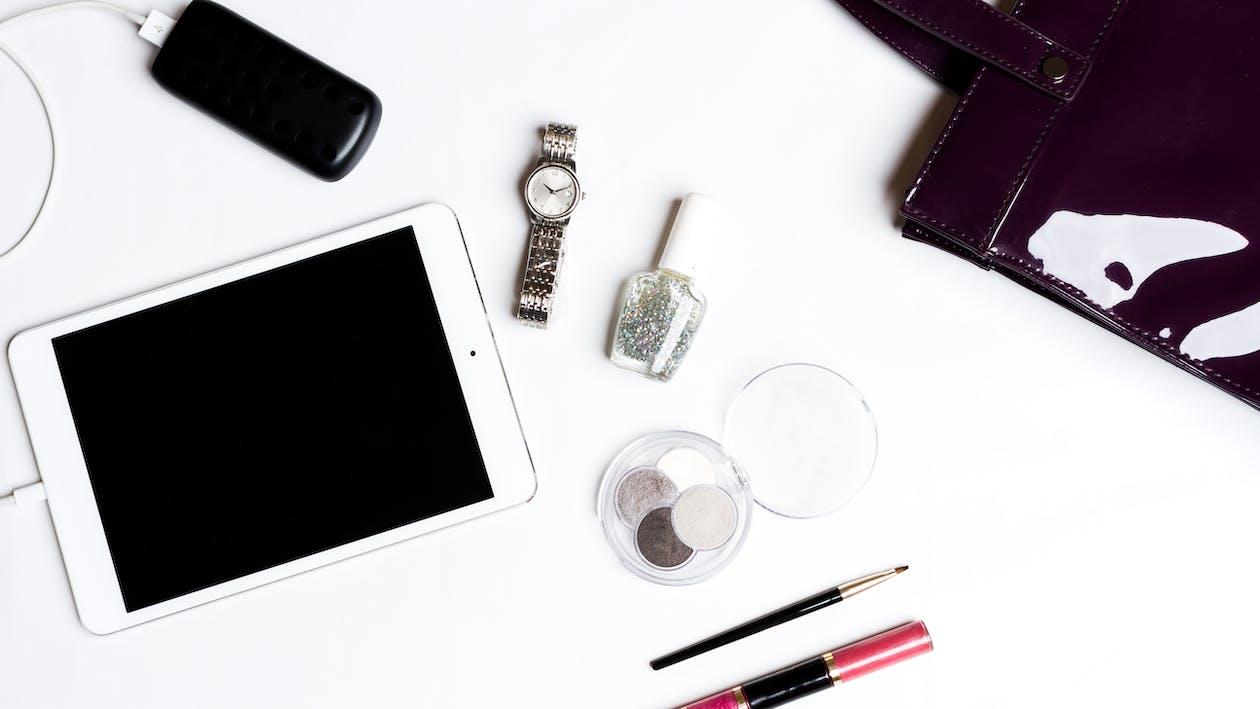 Ipad Blanco, Reloj Plateado, Smartphone Negro, Botella De Esmalte De Uñas Y Pincel De Maquillaje Negro Sobre Fondo Blanco.