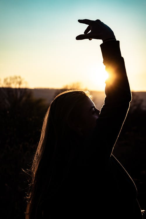Side View Silhouette Photo of Woman With Hand Raised
