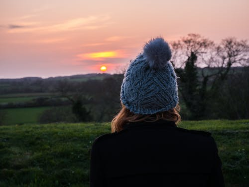 Back View Photo of Woman in Blue Knit Cap Overlooking Golden Horizon