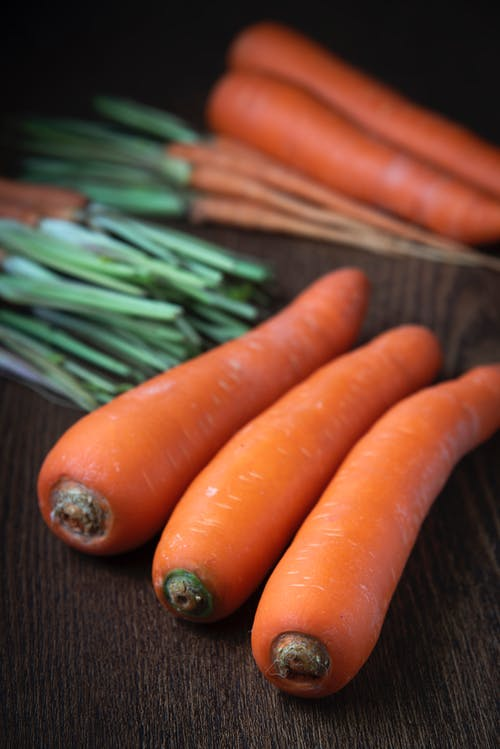 Selective Focus Close-up Photo of Carrots on Wooden Surface