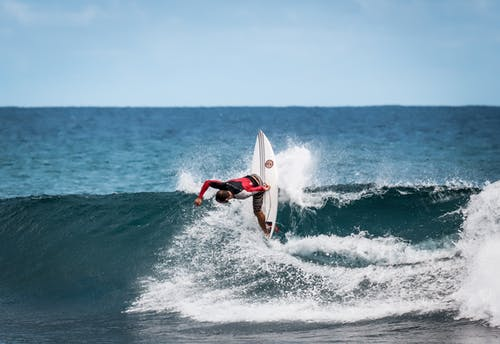 Person Wearing Red and Black Wetsuit Wave Surfing
