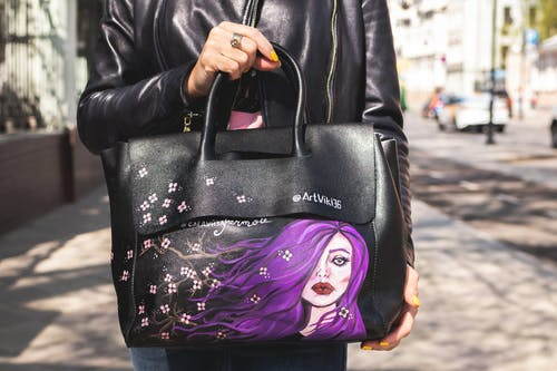 Person in Black Leather Jacket Carrying Black and Purple Leather Handbag
