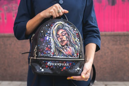 Person Holding Black and Multicolored Leather Backpack