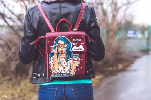 Person Wearing Red and Multicolored Leather Backpack