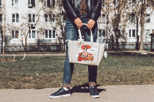 Person in Black Leather Jacket and Blue Denim Jeans Holding White Leather Tote Bag