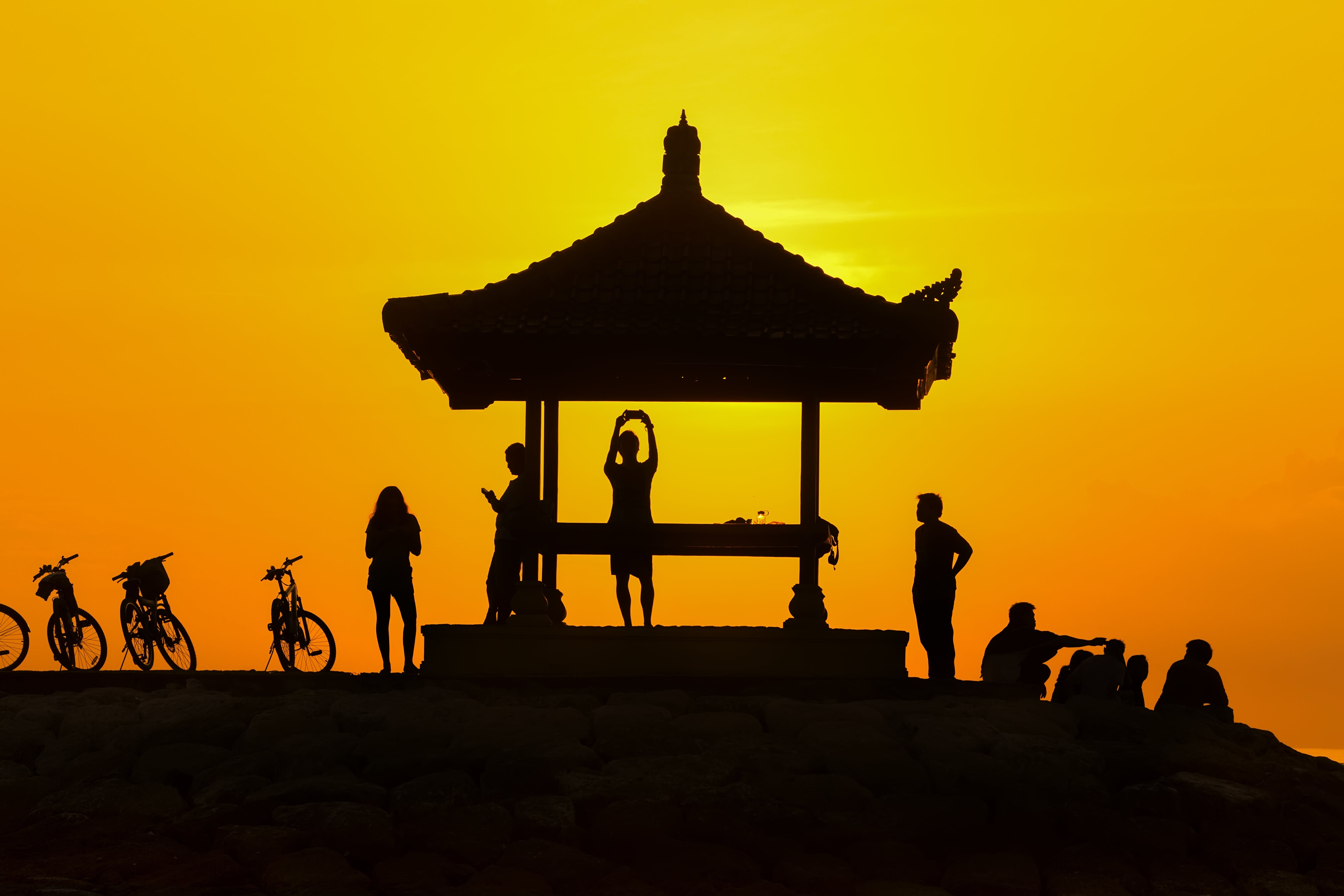 Silhouette of People Standing Near Gazebo