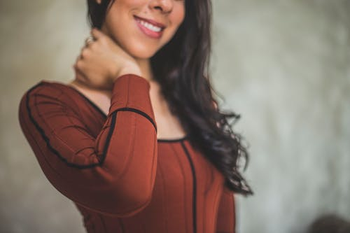 Smiling Woman Holding Neck Using Right Hand