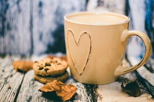 Beige Ceramic Heart Mug With Coffee Beside Cookie Food