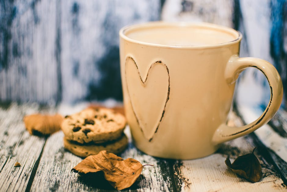 Beige Ceramic Heart Mug With Coffee Beside Cookie Food