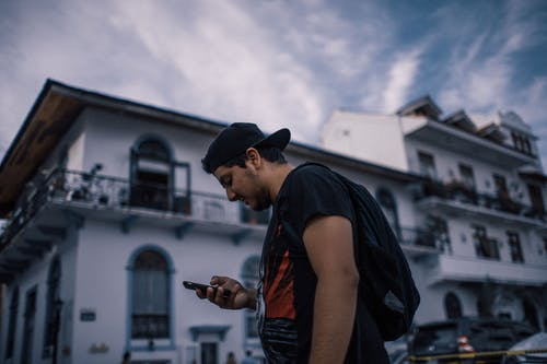 Side View Photo of Man in Black T-shirt Using Smartphone