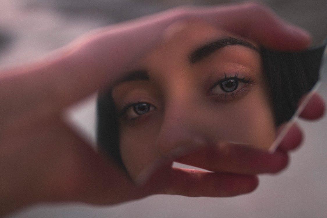 Shallow Focus Photo of Woman's Reflection on Broken Mirror