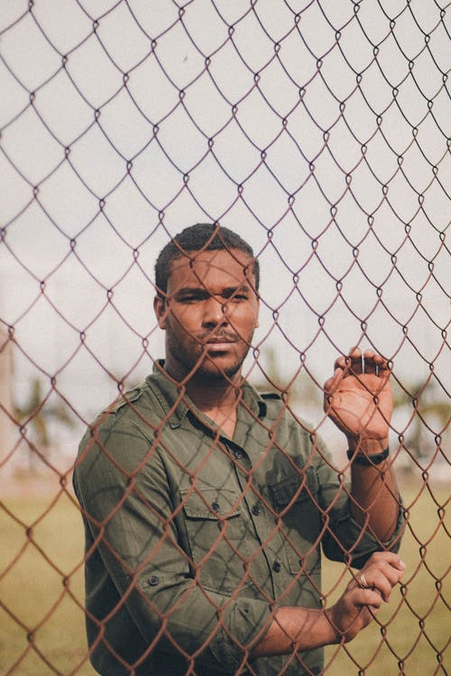 Man in Green Shirt Standing Behind Chain Link Fence