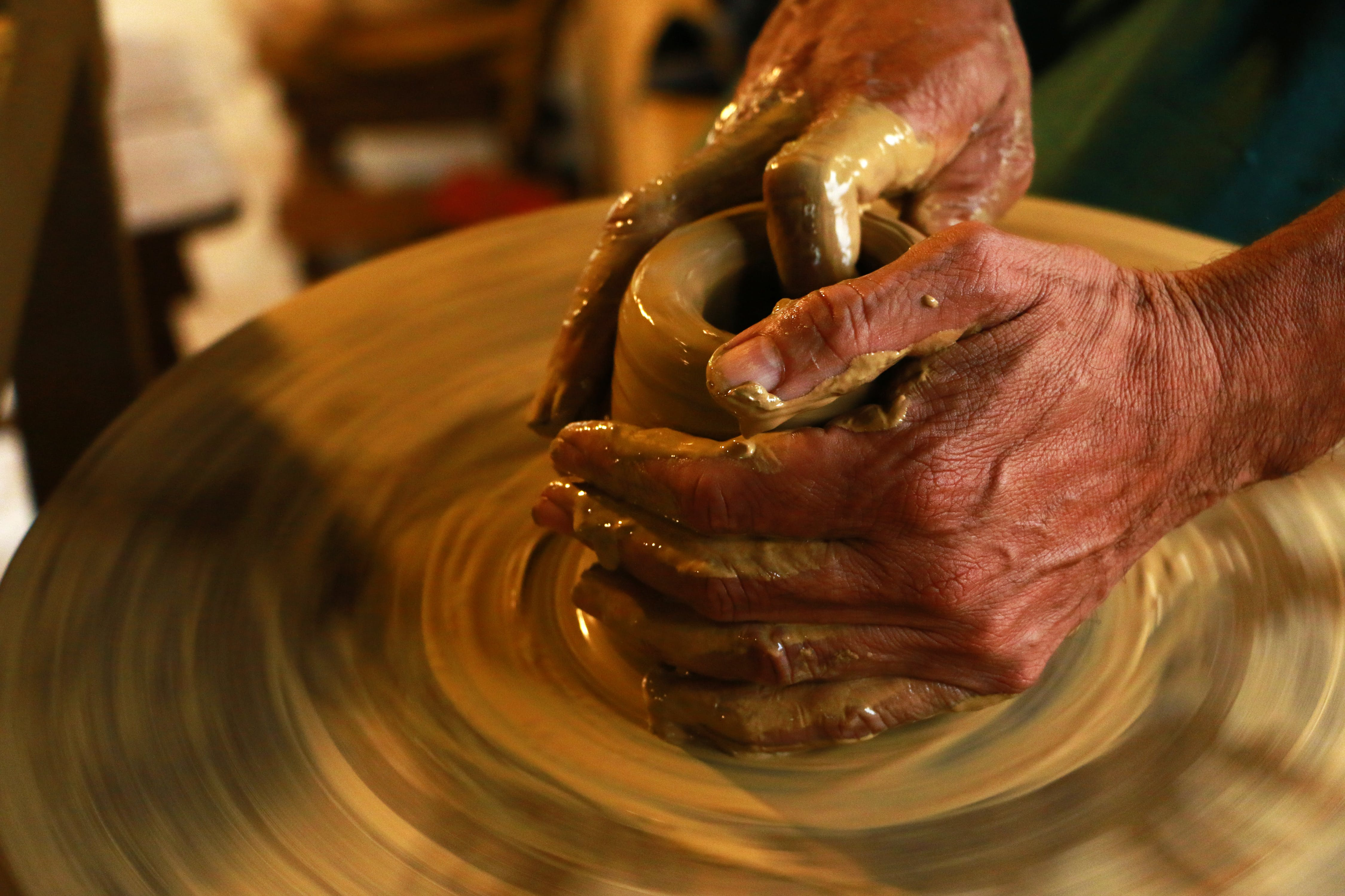 Selective Focus Photography of Person Molding Clay