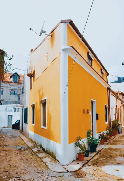 Yellow and White Concrete Roadside House