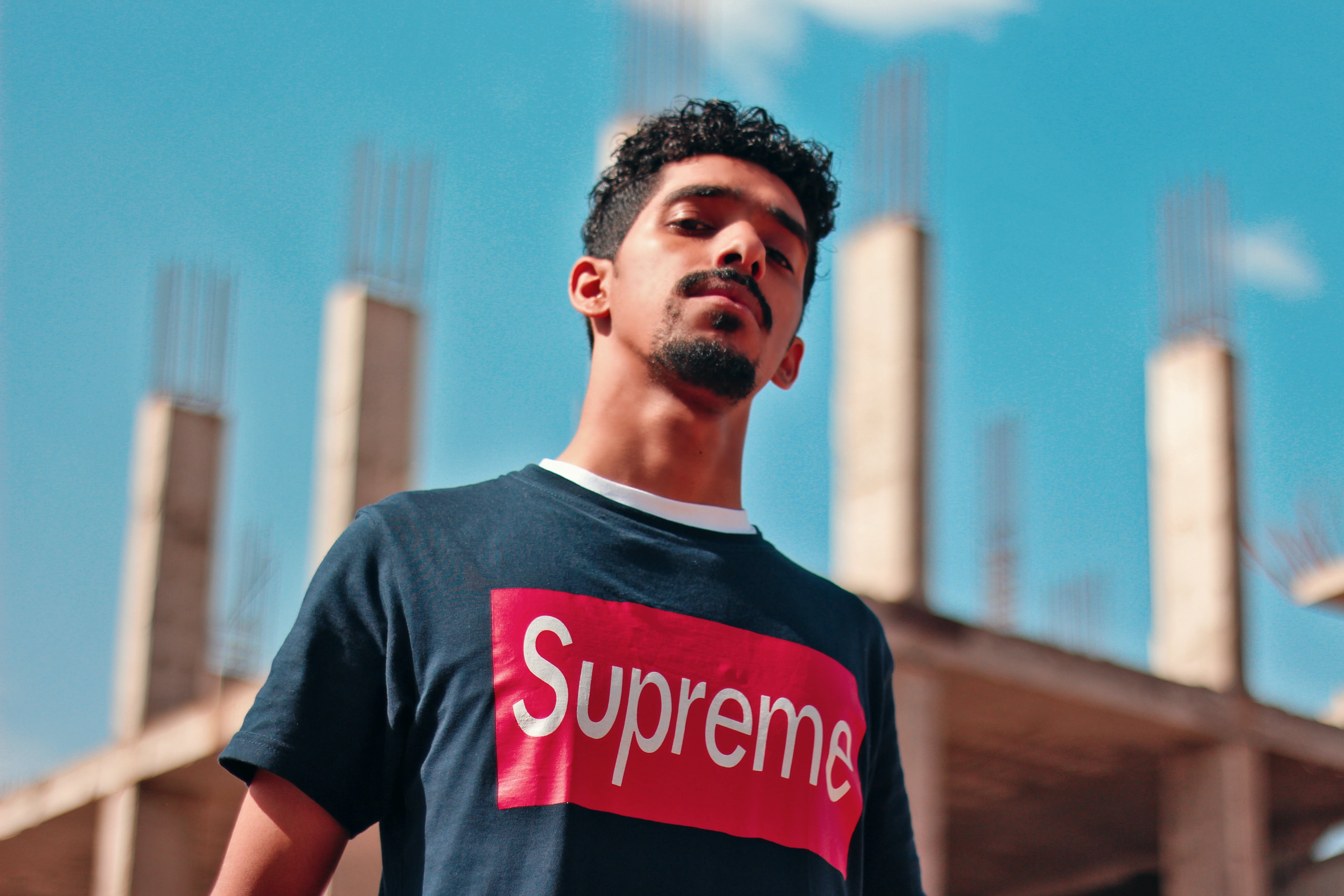Man Wearing Black and Red Supreme Shirt Standing by the Constructed Building