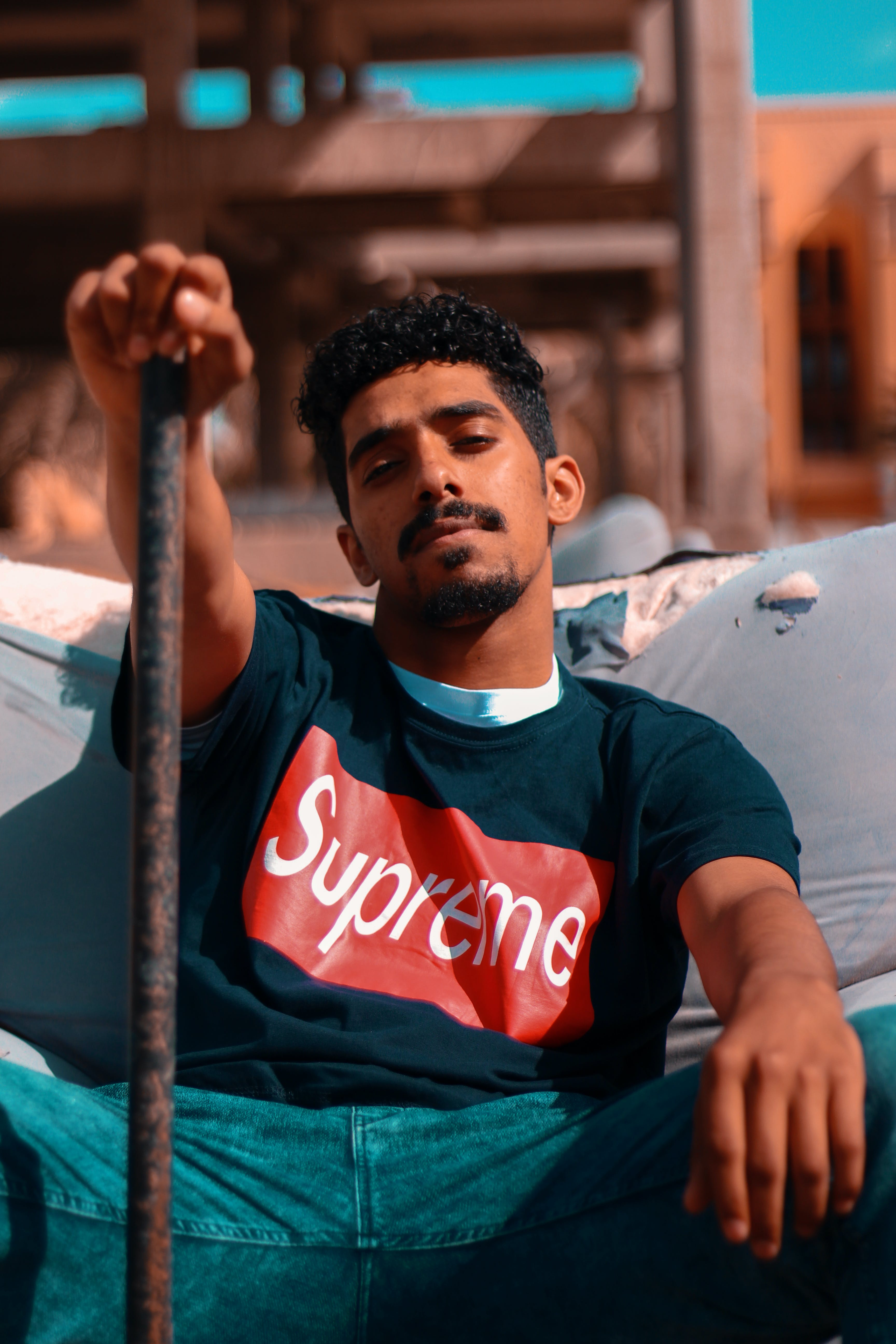 Man Sitting on Sofa Holding Brown Metal Bar