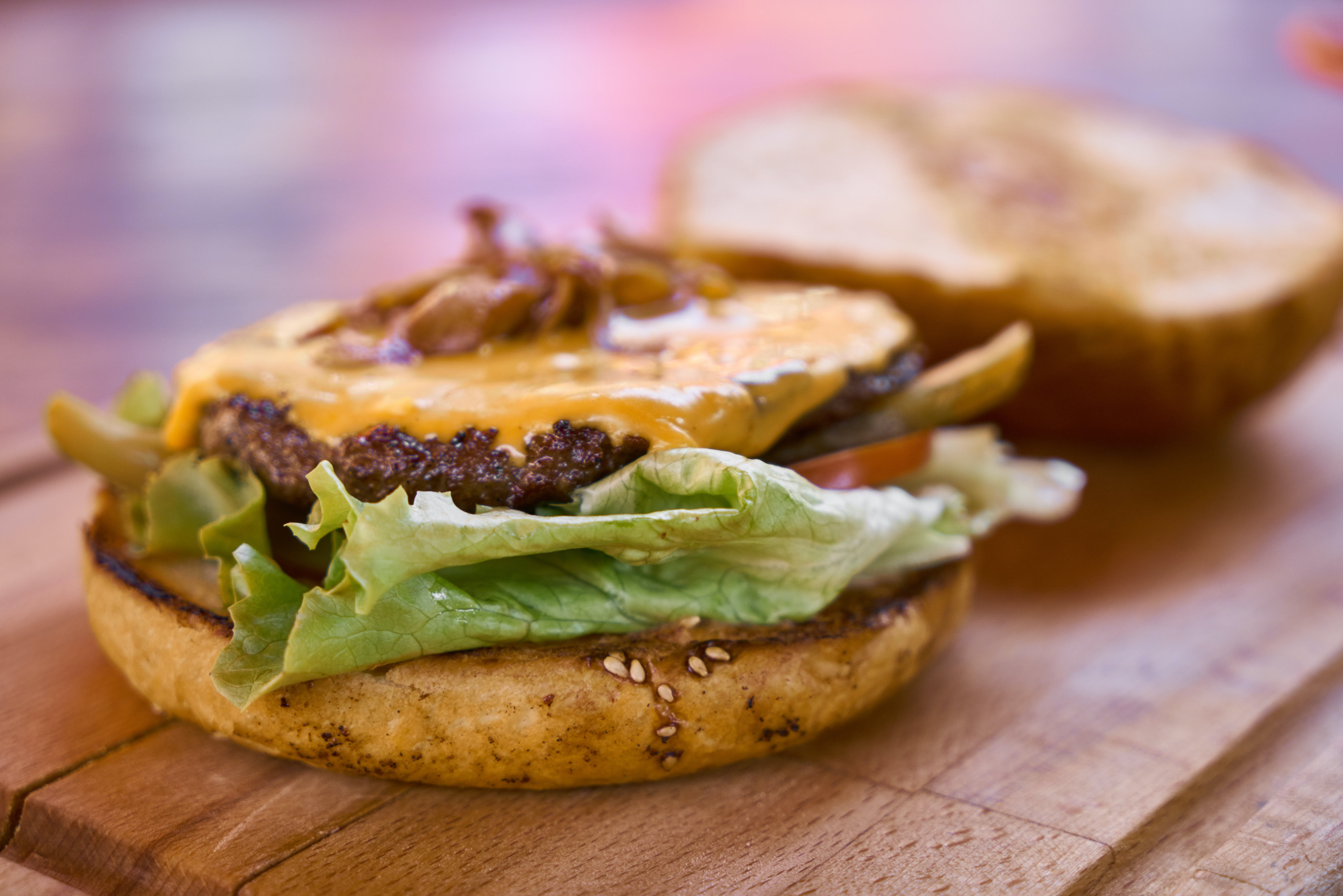Hamburger With Top Bun Taken Off on Wooden Table