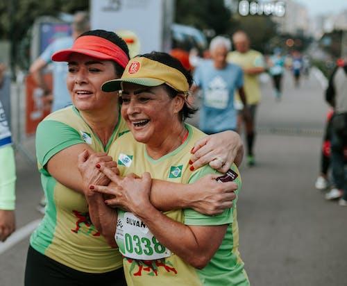 Two Smiling Women Wearing Yellow-and-green Shirts