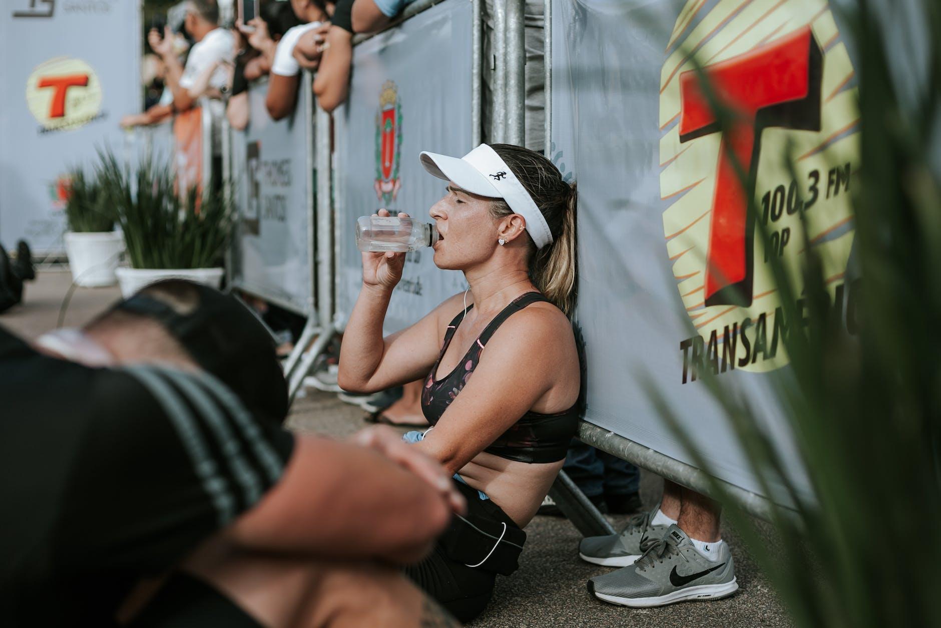 Tips voor afvallen toegepast door een marathon-loper, die vermoeid uit een flesje water drinkt.
