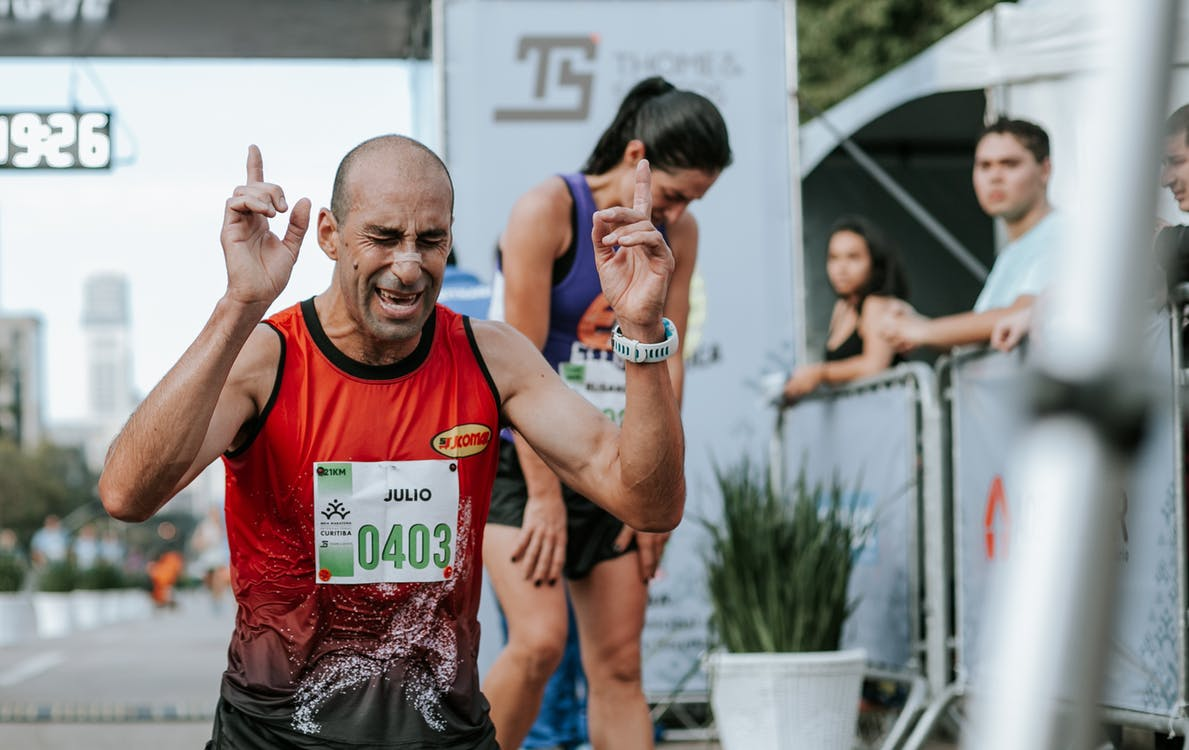 Man in Red Tank Top Winning A Marathon
