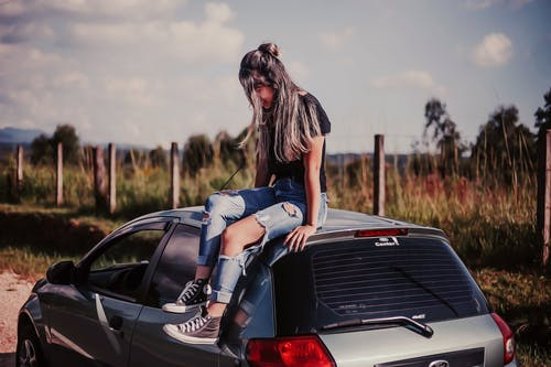 Woman Wearing Black Shirt And Blue Denim Jeans Sitting On Vehicle Roof