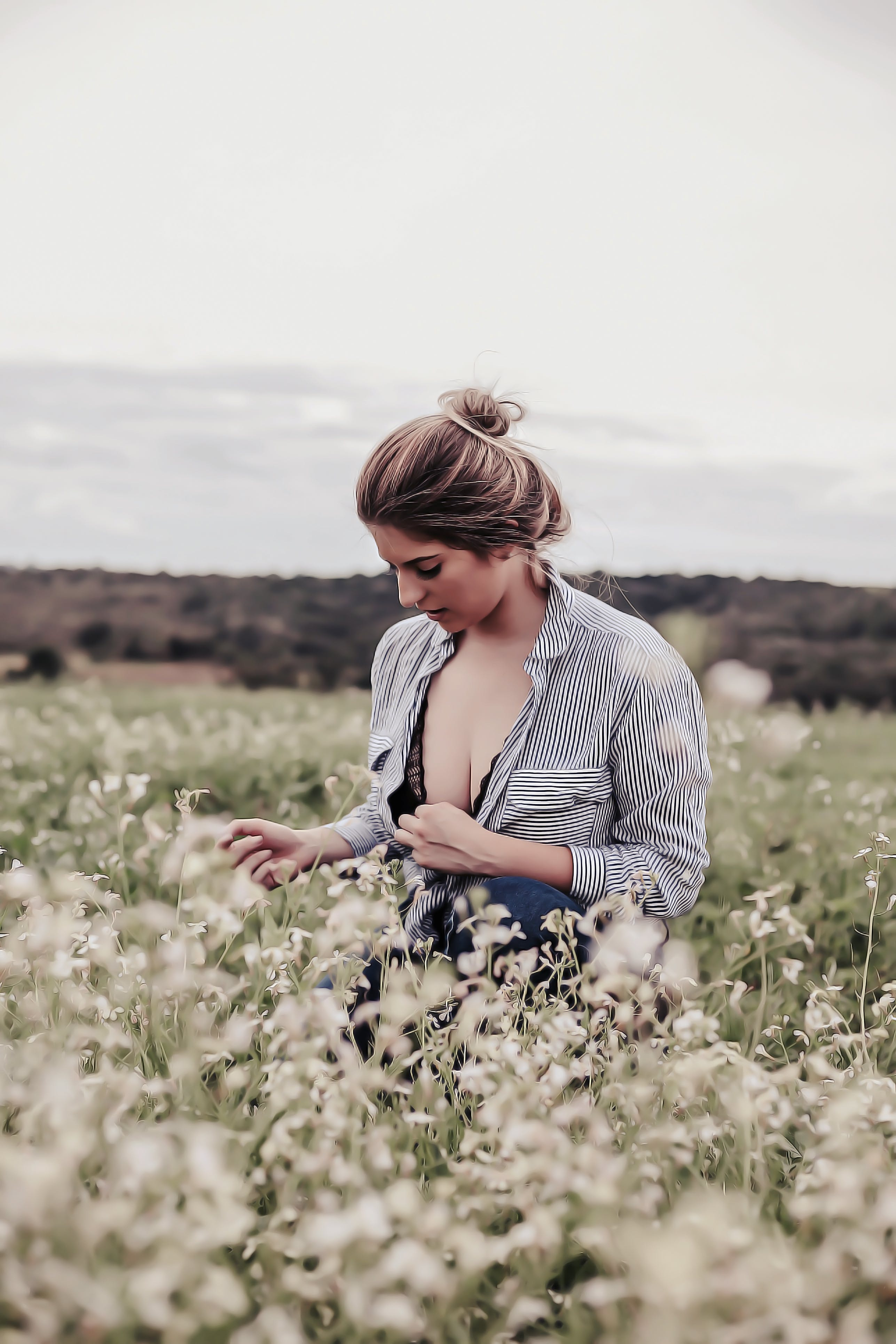 Photo of Woman With Opened Cleavage Knelling in the Middle of Grass Field