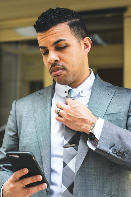 Man in Gray Suit Jacket Using Black Smartphone