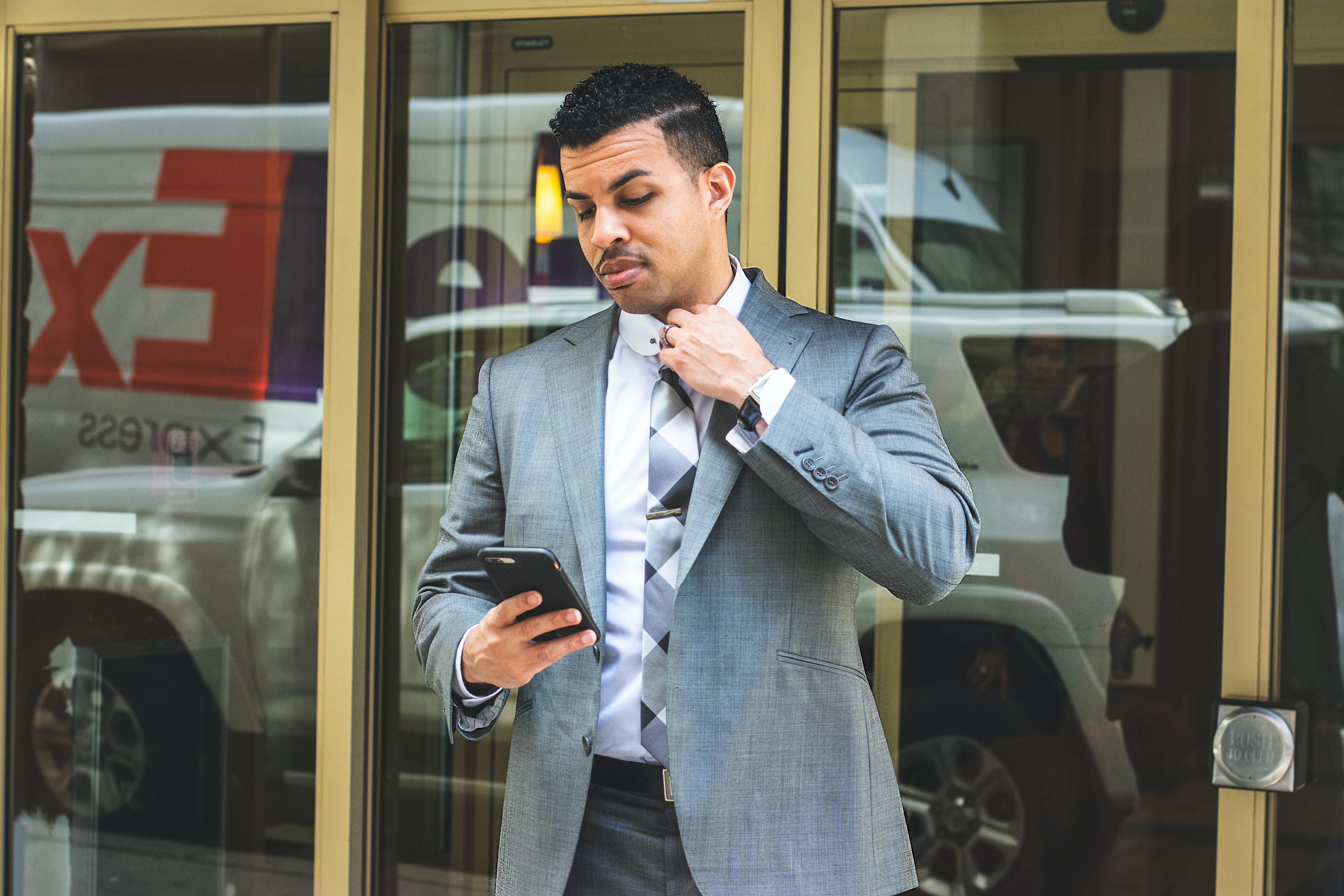 Man Wearing Gray Suit Holding Black Smartphon