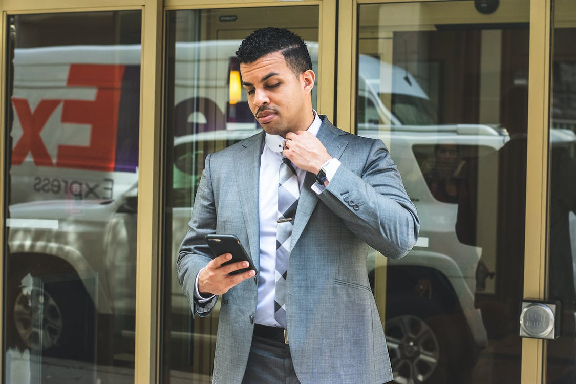 Man Wearing Gray Suit Holding Black Smartphon