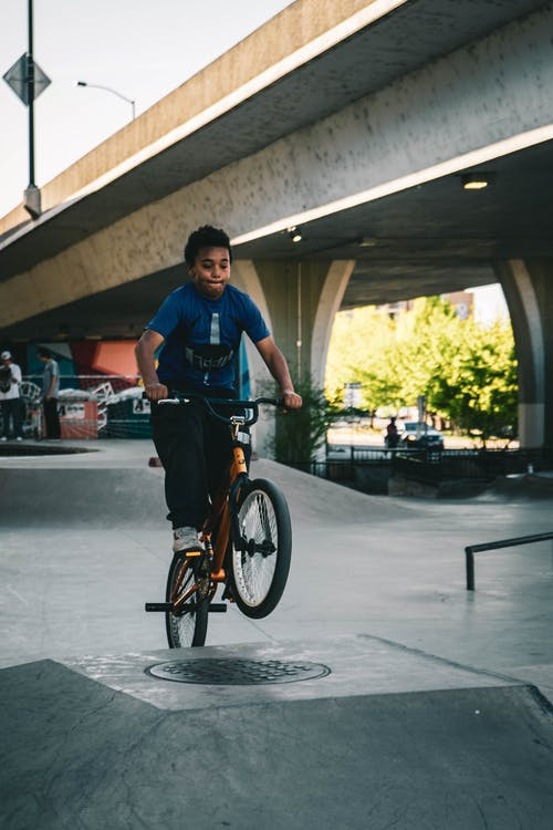 Boy in Blue Shirt Riding Bike on Ramp