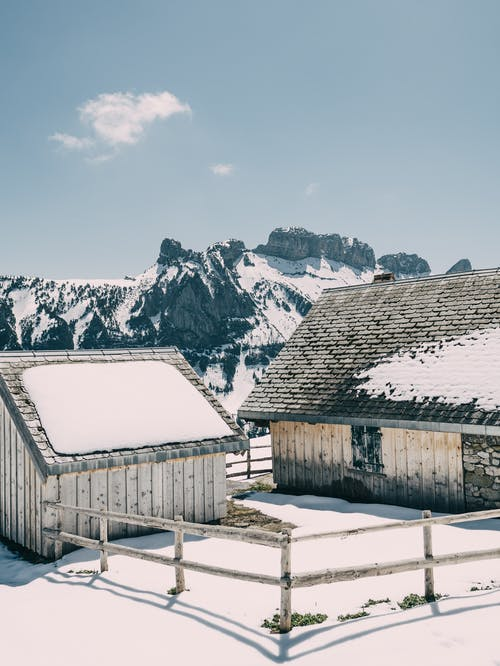 Two White Wooden Houses Near Snow Mountain