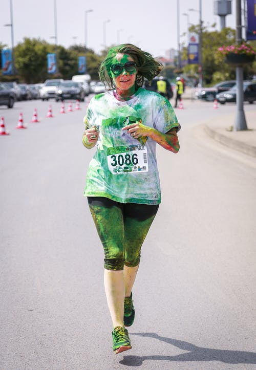 Woman Wearing White Shirt Covered With Green Powder While Jogging on Road