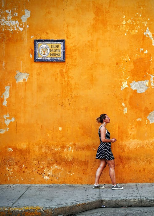 Woman Standing Beside Orange Wall