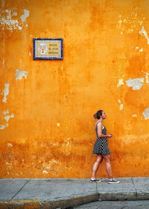 Woman Standing Beside Orange Wall