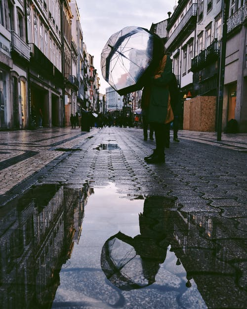 Person Standing on Street Near Puddle