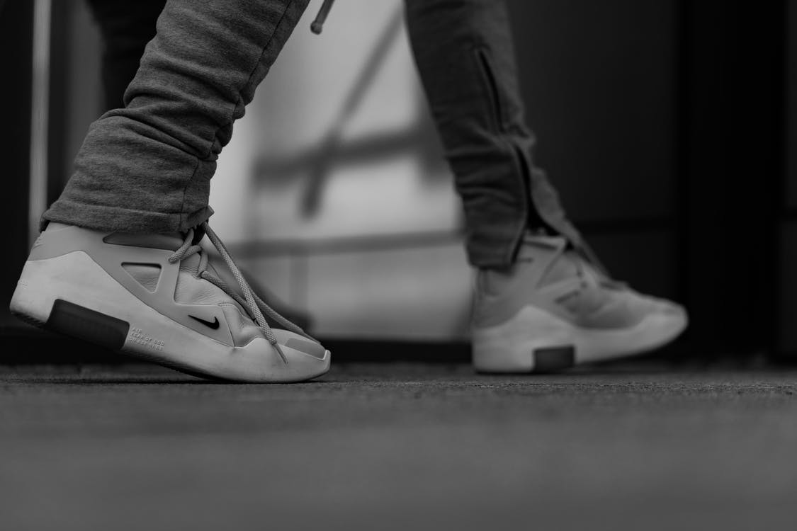 Grayscale Photography Of Person In White Nike Sneakers