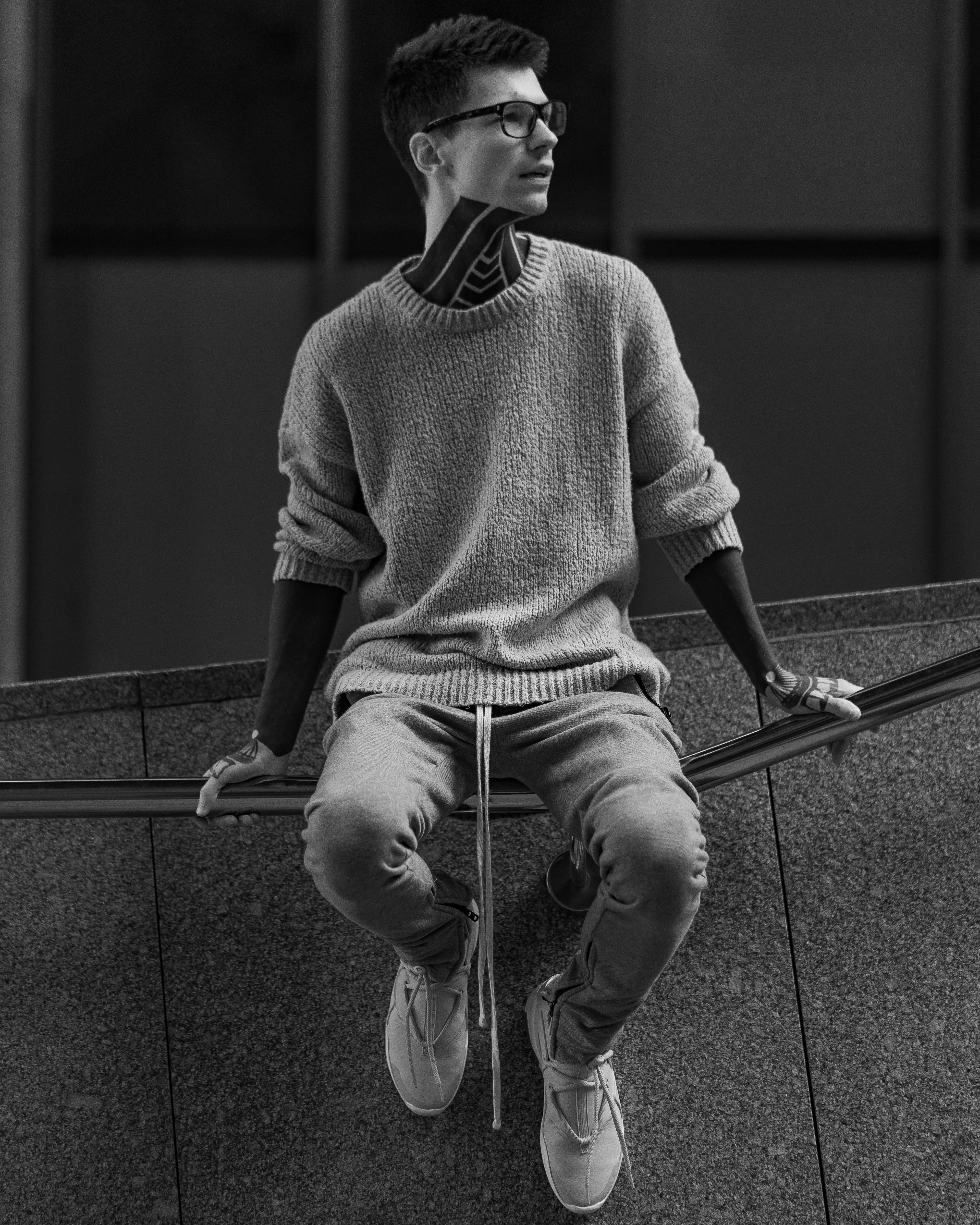 Grayscale Photo Of Man Sitting On Handrail