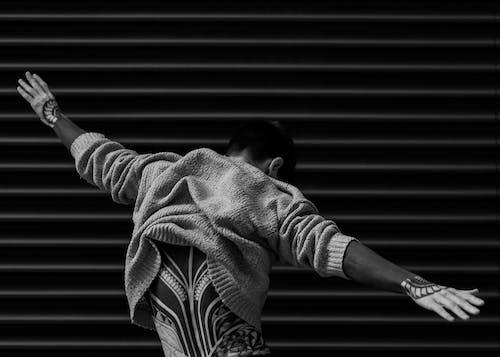 Monochrome Photo of Man Raising His Hands